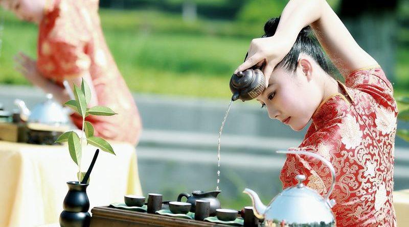 китайцы пьют кипяток китаянка наливает через голову чай
